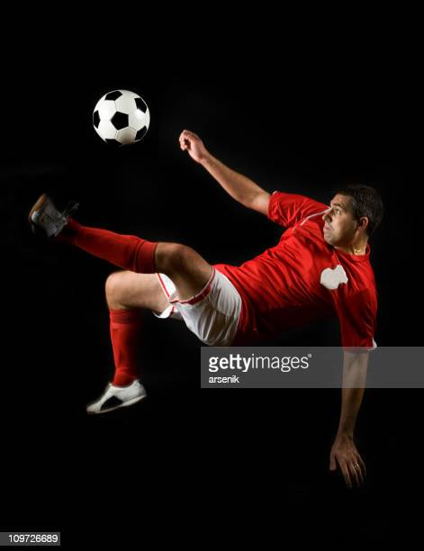 Soccer Player Doing Flying Kick with Ball, Isolated on Black