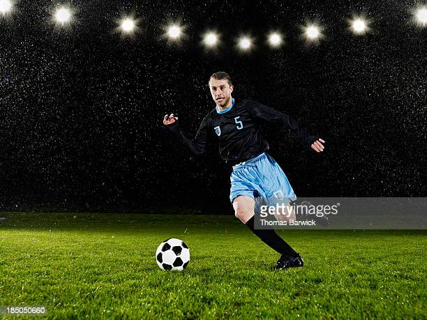 Soccer player dribbling ball down field