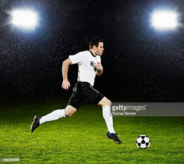 soccer player dribbling ball down field - dribbling sports stock pictures, royalty-free photos & images