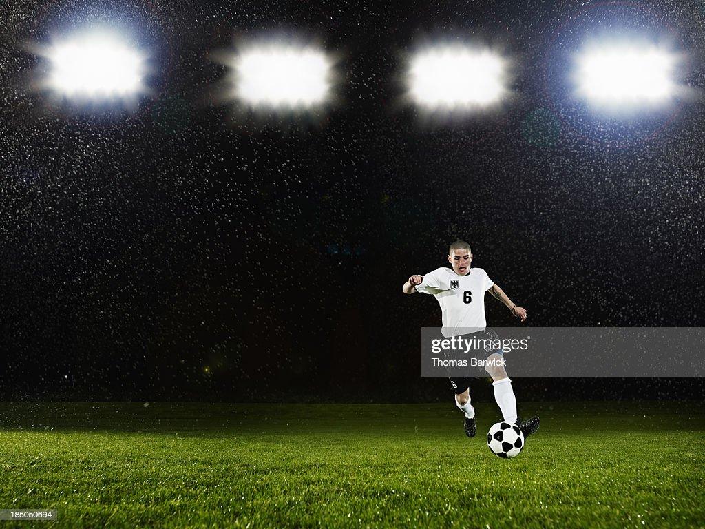 Soccer player dribbling ball on field in rain : Stock Photo