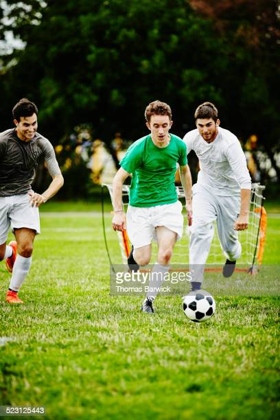 soccer player dribbling ball past opposing players - rush american football stock pictures, royalty-free photos & images