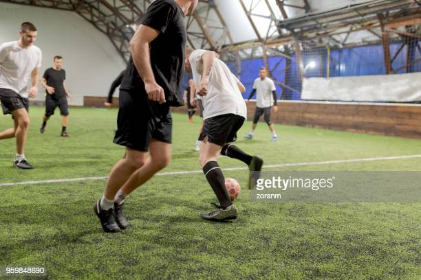 soccer player dribbling ball past opposing players - amateur stock pictures, royalty-free photos & images