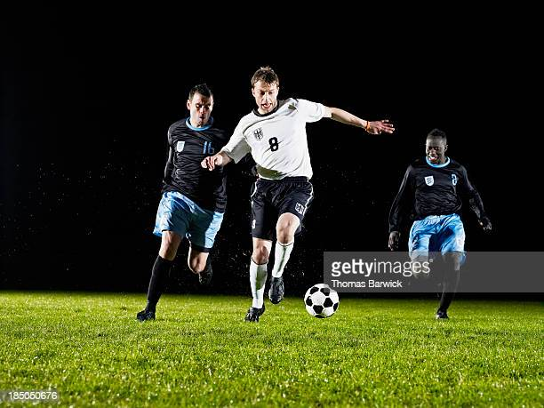 soccer player dribbling ball past opposing team - passing sport stock pictures, royalty-free photos & images