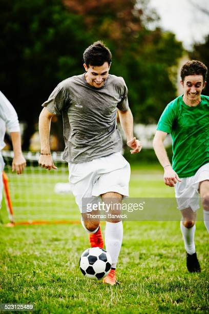 Soccer player dribbling ball pursued by opponents