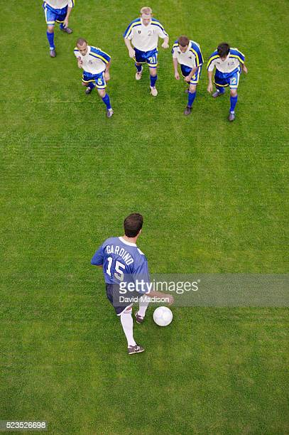 soccer player dribbling toward defenders - confrontation stock pictures, royalty-free photos & images