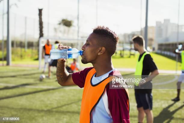 Footballeur boire de l'eau sur le terrain