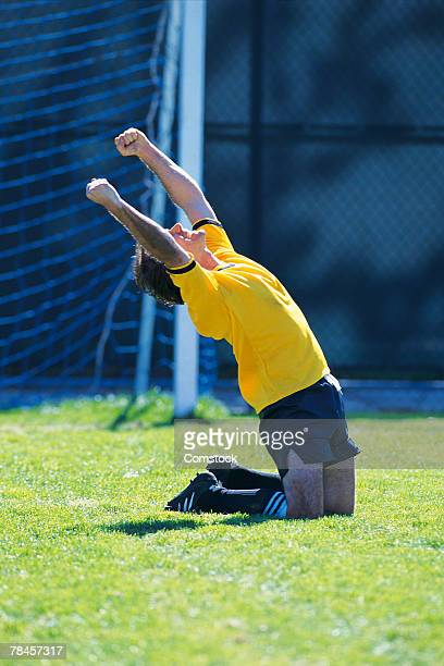 Soccer player exalting after scoring goal