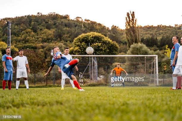 fußballer bekommen krämpfe im beinmuskel und andere spieler hilft ihm - punkten stock-fotos und bilder