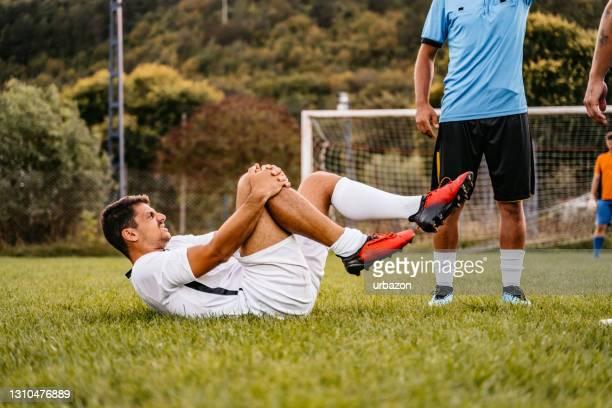 fußballer verletzt sich im spiel - sportlicher zweikampf stock-fotos und bilder