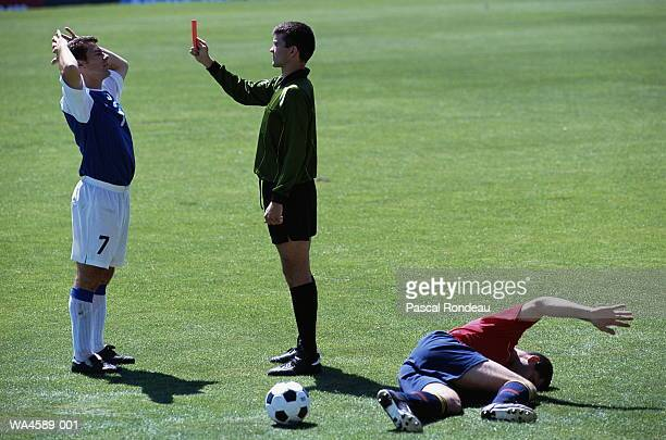 Soccer player getting red card, opposing player on ground