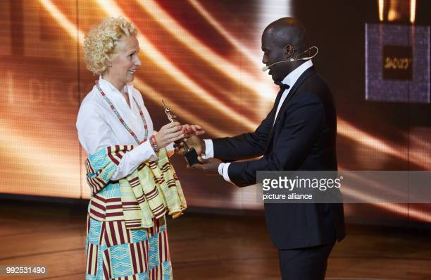 "Soccer player Hans Sarpei presents an award to Bettina Landgrafe during the the award ceremony of the ""Goldene Bild der Frau"" in Hamburg, 21 October..."