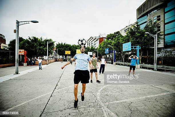 Soccer player heading ball during pick up game