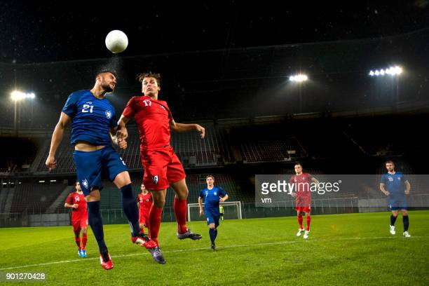soccer player heading the ball - football player stock pictures, royalty-free photos & images
