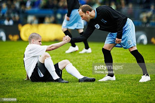 soccer player helping opposing player up - rivaliteit stockfoto's en -beelden
