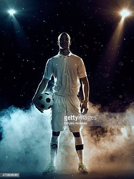 Soccer player holding a ball amidst smoke and spotlights