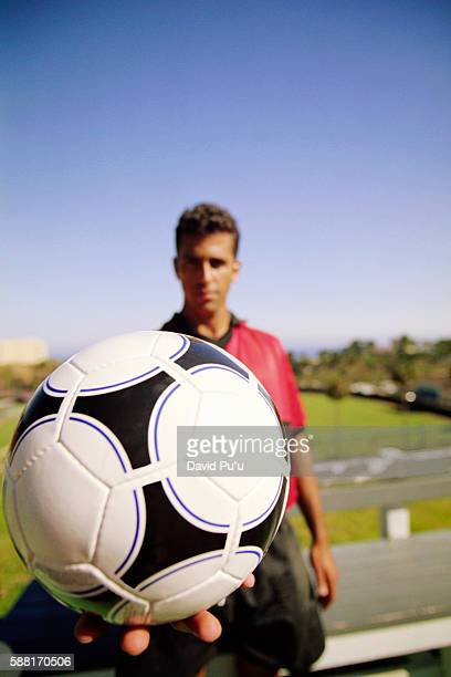 Soccer Player Holding Ball in Palm