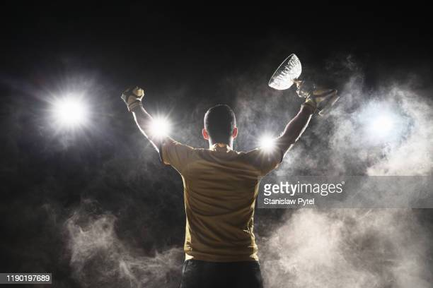soccer player holding crystal cup and celebrating victory on smoky background - winnen stockfoto's en -beelden