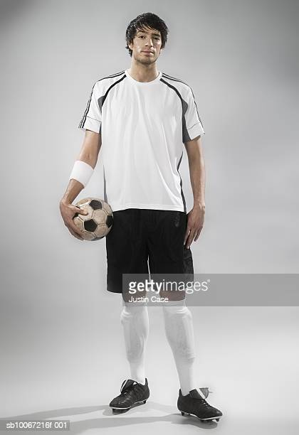 Soccer player holding soccer ball, studio shot, portrait