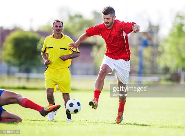 Joueur de football en action sur un terrain de jeu.