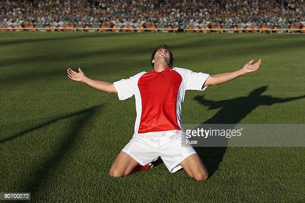 soccer player in joyous celebration - redding sporten stockfoto's en -beelden