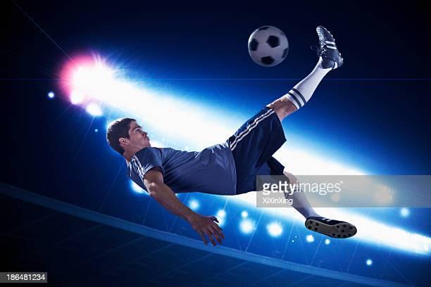 soccer player in mid air kicking the soccer ball, stadium lights at night in background - fußball wettbewerb stock-fotos und bilder