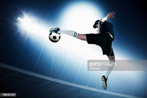 soccer player in mid air kicking the soccer ball, stadium lights at night in background - essayer de marquer photos et images de collection