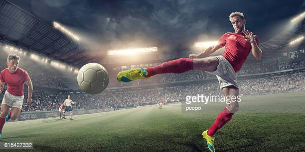 Soccer Player in Mid Air Volley Action During Football Match