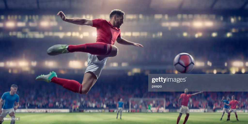 Soccer Player In Mid Air Volley Ball During Football Match : Stock Photo