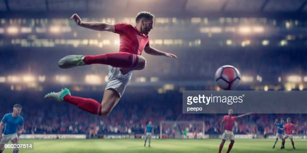 soccer player in mid air volley ball during football match - match sportivo foto e immagini stock