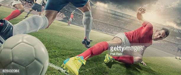 soccer player in sliding tackle during football match in stadium - tackling stock pictures, royalty-free photos & images