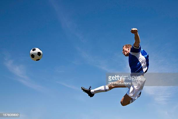 soccer player in the air kicking ball - shooting at goal stock pictures, royalty-free photos & images