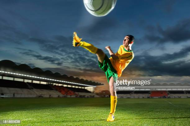 Soccer player is kicking the ball hard in stadium