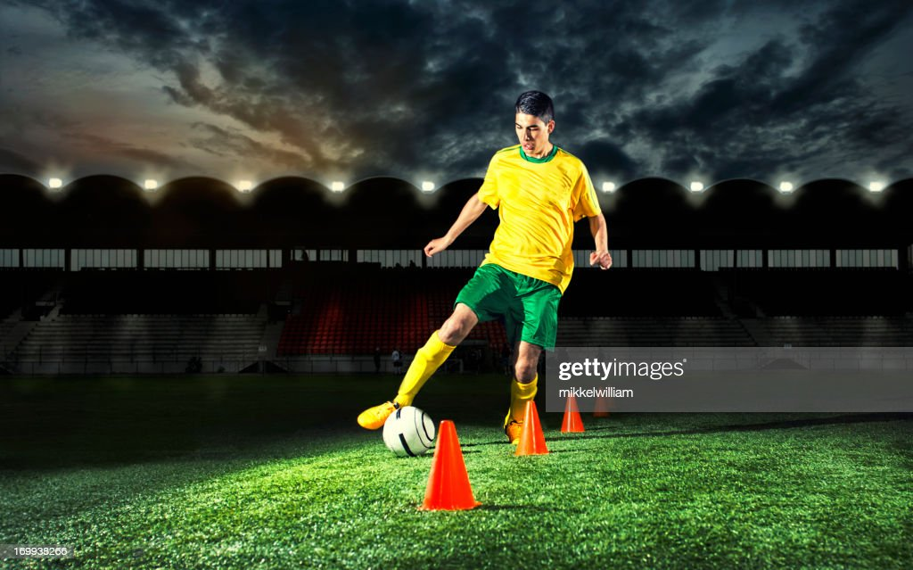 Soccer player is training with plastic cones at night : Stock Photo