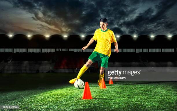 soccer player is training with plastic cones at night - cone shape stock photos and pictures