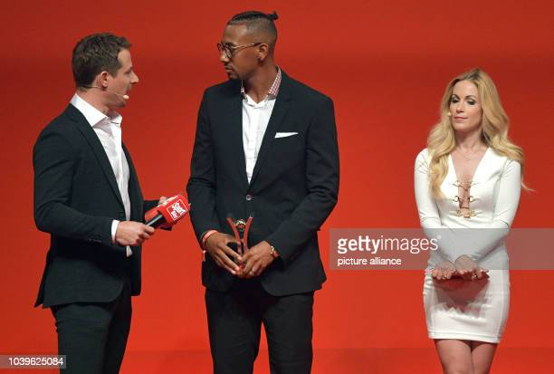 Soccer player Jerome Boateng stands on stage with presenters Alexander Bommes and Andrea Kaiser at the Sport BildAward ceremony in Hamburg Germany 29...