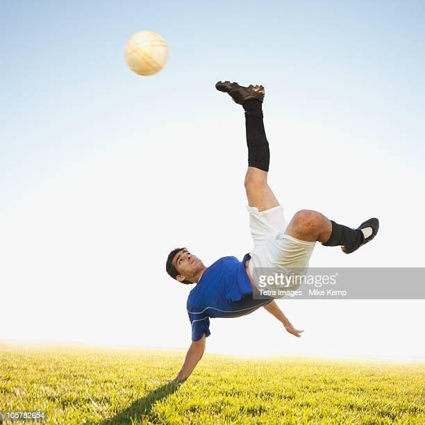 Soccer player jump kicking