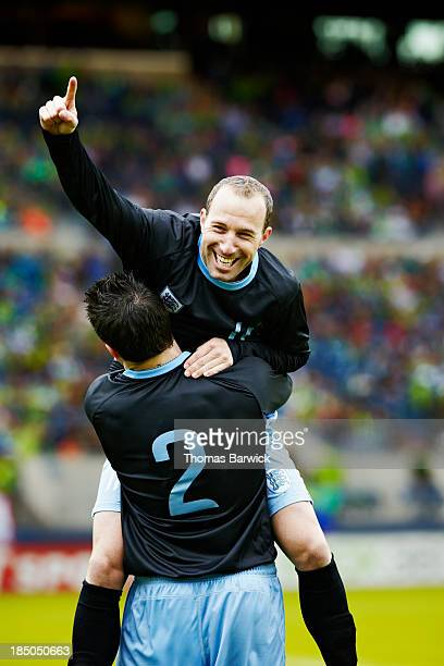Soccer player jumping into the arms of teammate