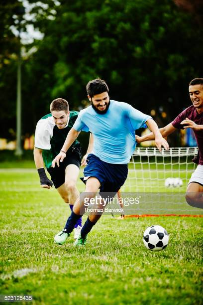 soccer player keeping ball away from opponents - rush american football stock pictures, royalty-free photos & images