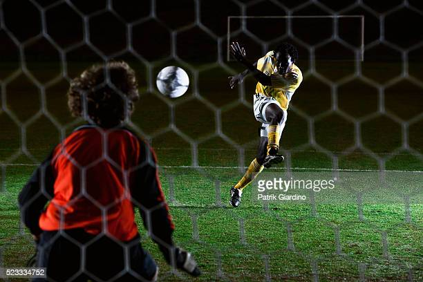 soccer player kicking a goal - segnare foto e immagini stock