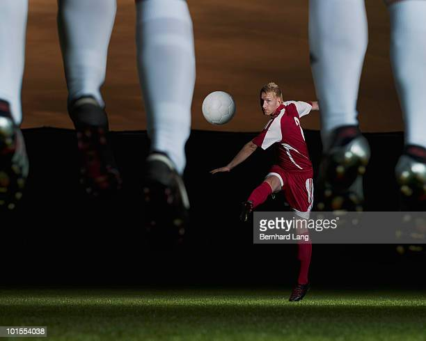 Soccer player kicking ball against defence wall
