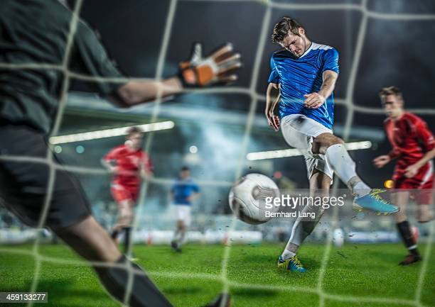 soccer player kicking ball at goal - marquer un but photos et images de collection