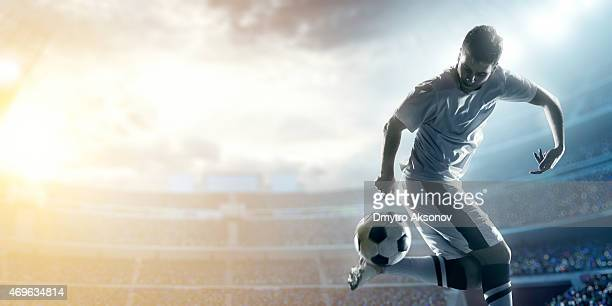 giocatore di calcio calciare la palla in stadium - calciatore foto e immagini stock
