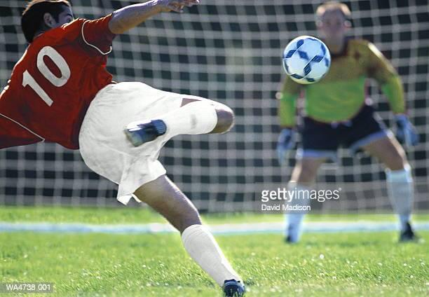 soccer player kicking ball, goalie and net in background - ショットを決める ストックフォトと画像