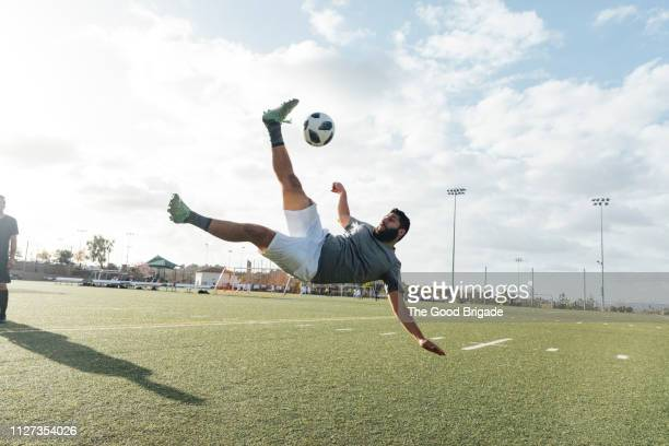 soccer player kicking ball in mid air - kicking stock pictures, royalty-free photos & images