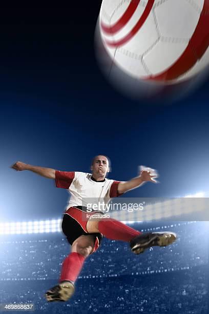 サッカー選手ボールを蹴るミッド air - ショットを決める ストックフォトと画像