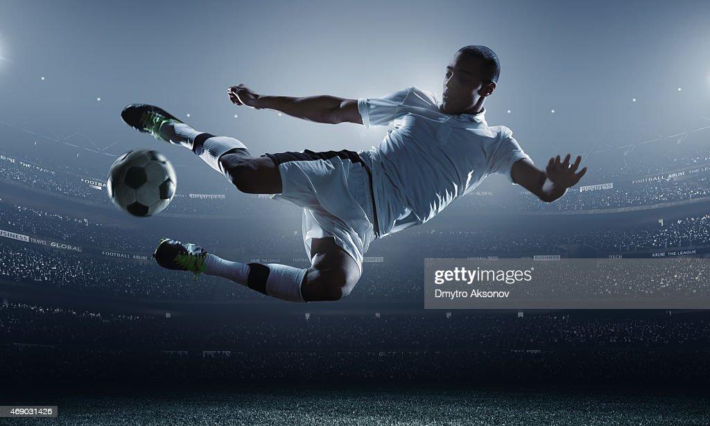 Soccer player kicking ball in stadium : Stock Photo
