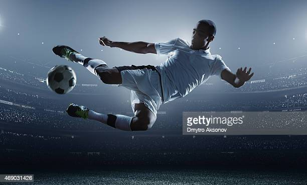 soccer player kicking ball in stadium - scoring a goal stock pictures, royalty-free photos & images