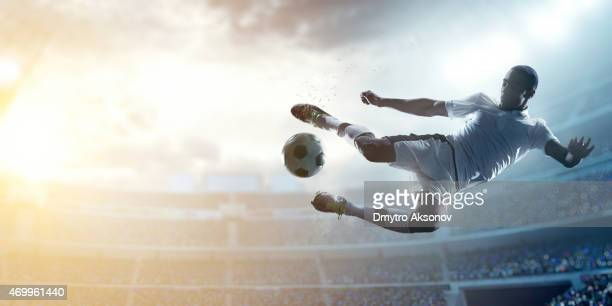 soccer player kicking ball in stadium - football stock pictures, royalty-free photos & images