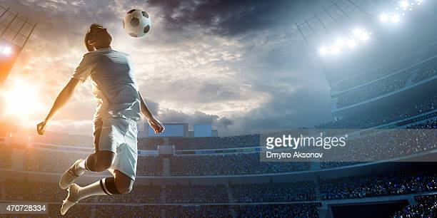 soccer player kicking ball in stadium - football player stock pictures, royalty-free photos & images