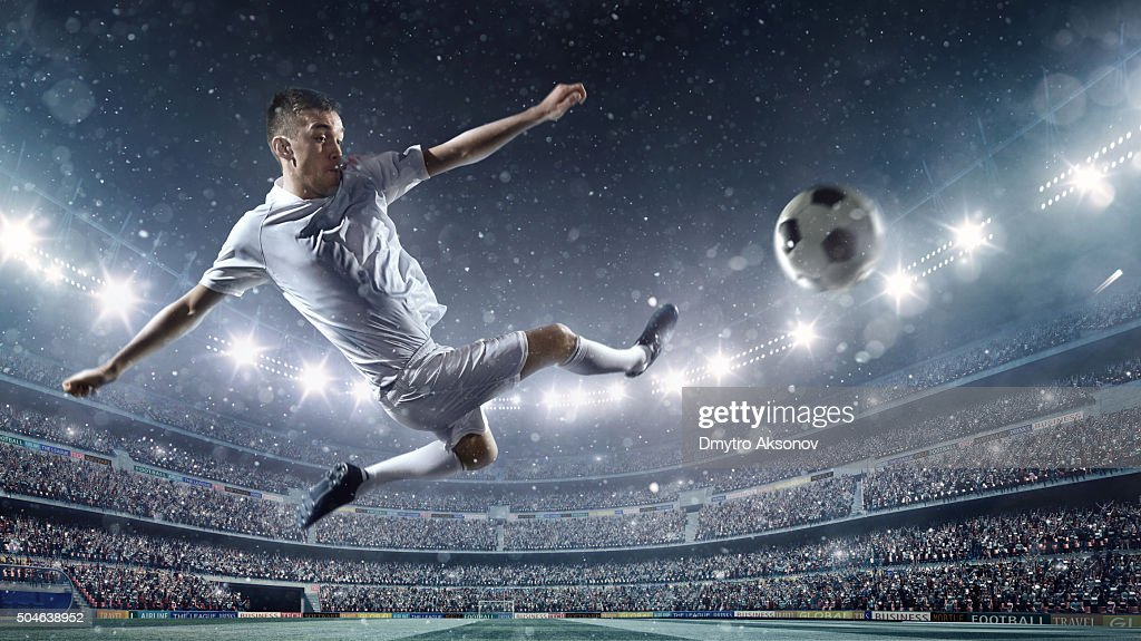 Soccer player kicking ball in stadium : Stock Photo